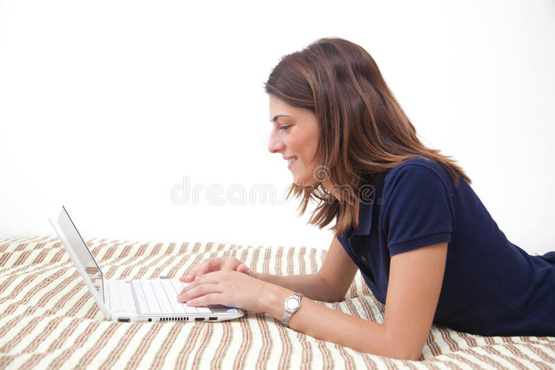 Beautiful girl on the bed with her laptop stock photography