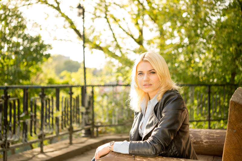 Beautiful girl on a bench in the sun stock photography