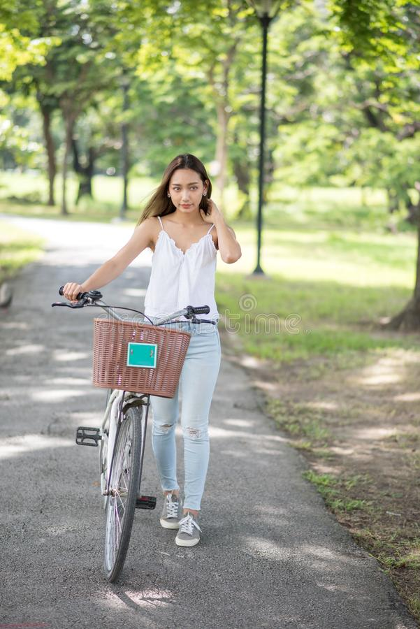 Beautiful girl with bicycle in park stock image