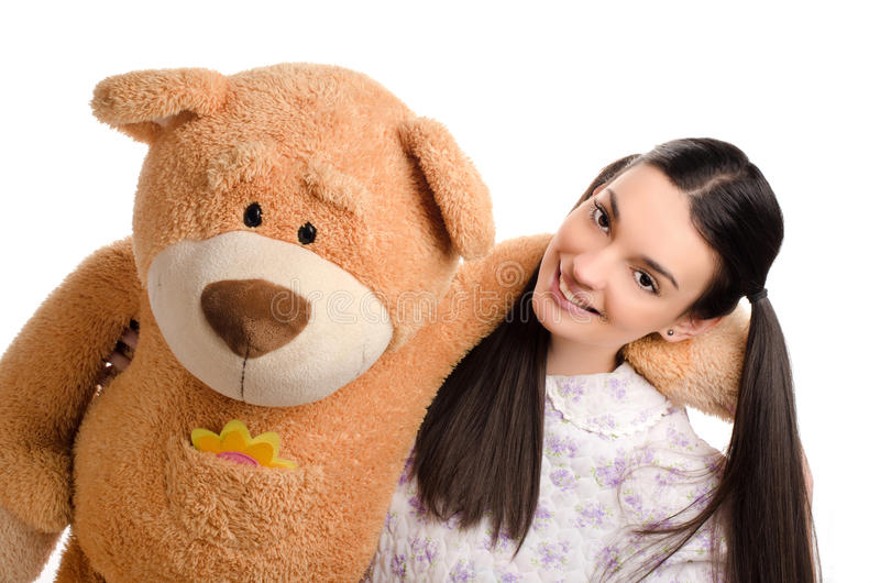 Beautiful girl with a big teddy bear. Happy brunette girl playing with a big teddy bear stock photography