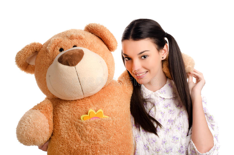 Beautiful girl with a big teddy bear. Happy brunette girl playing with a big teddy bear royalty free stock images