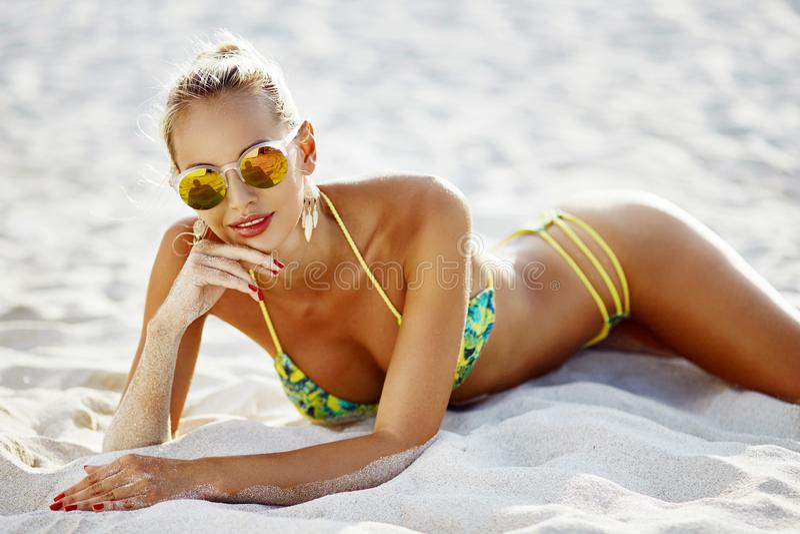 Beautiful girl in bikini and sunglasses lying on a sand royalty free stock photos