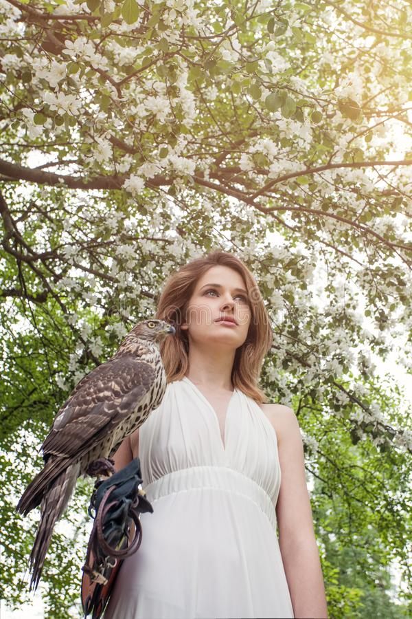 Beautiful girl with bird outdoors portrait in spring blossom garden stock photos