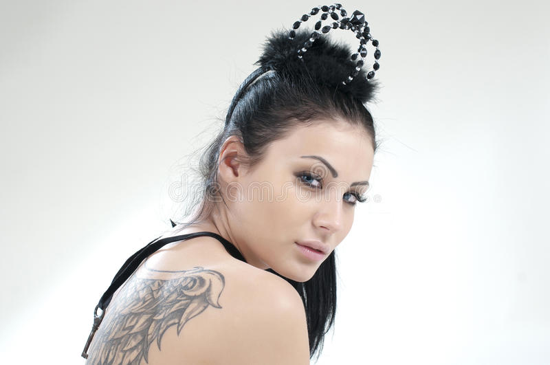 Beautiful girl with a black crown on her head. And tattoo wings on her back royalty free stock photography