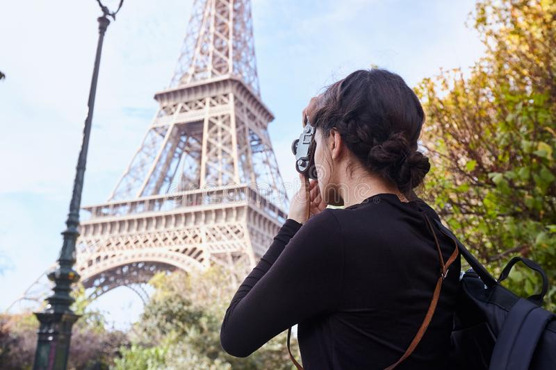 Beautiful girl posing with a camera taking pictures of the Eiffel Tower. Paris, Champ de Mars royalty free stock photography