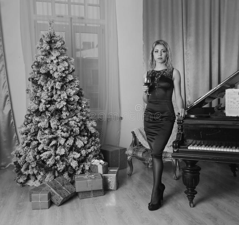 Beautiful girl in black dress on Christmas eve one, black white. wine. Black is white, night at the Christmas tree posing a spicy girl in evening dress and a stock image