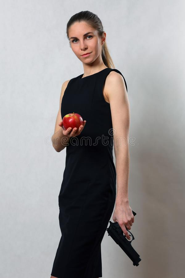 Beautiful girl in black dress with gun and Apple stock photography