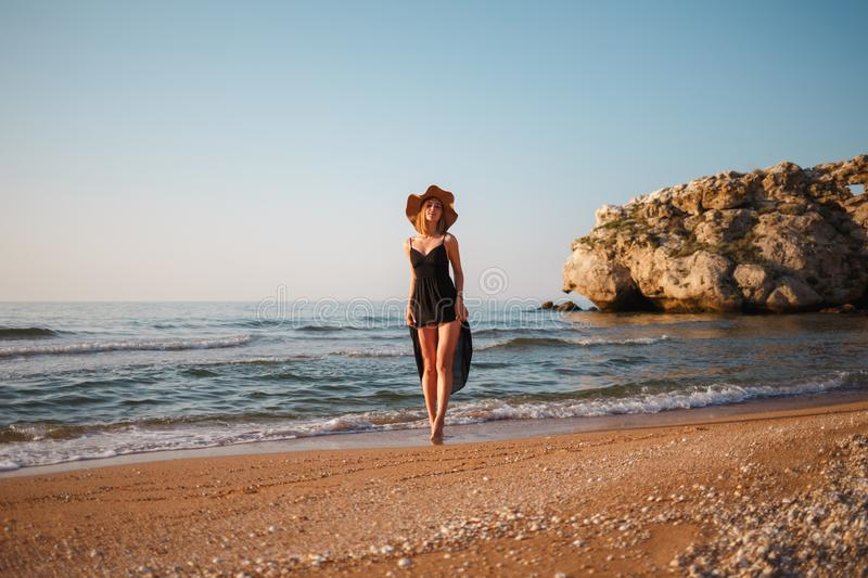 Beautiful girl in a black dress and hat walks along the sea sandy shore at sunset.  royalty free stock photo