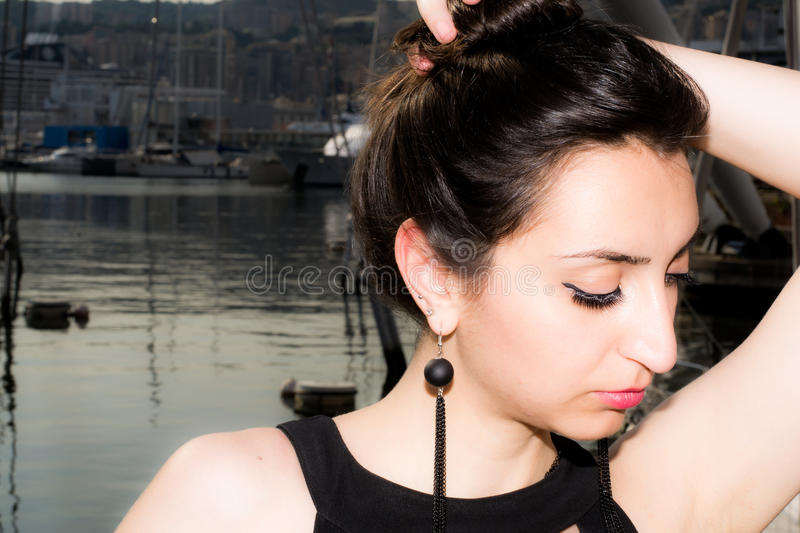 Beautiful girl with black dress holding her hair up with one hand stock images