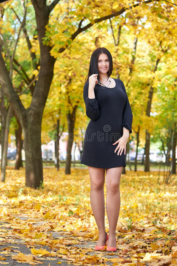 Beautiful girl in black dress and red shoes in yellow city park, fall season stock images