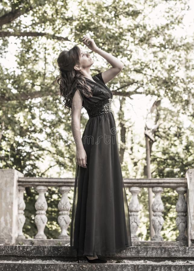Beautiful girl in a black evening dress near the stairwell of an abandoned palace. Beautiful woman with scars. Young girl in retro stock photography