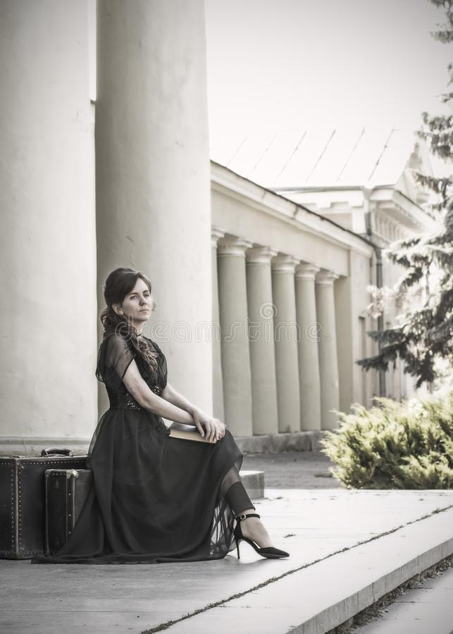 Beautiful girl in a black evening dress sits with a book. A girl sits with suitcases near an old building with columns. Beautiful stock images