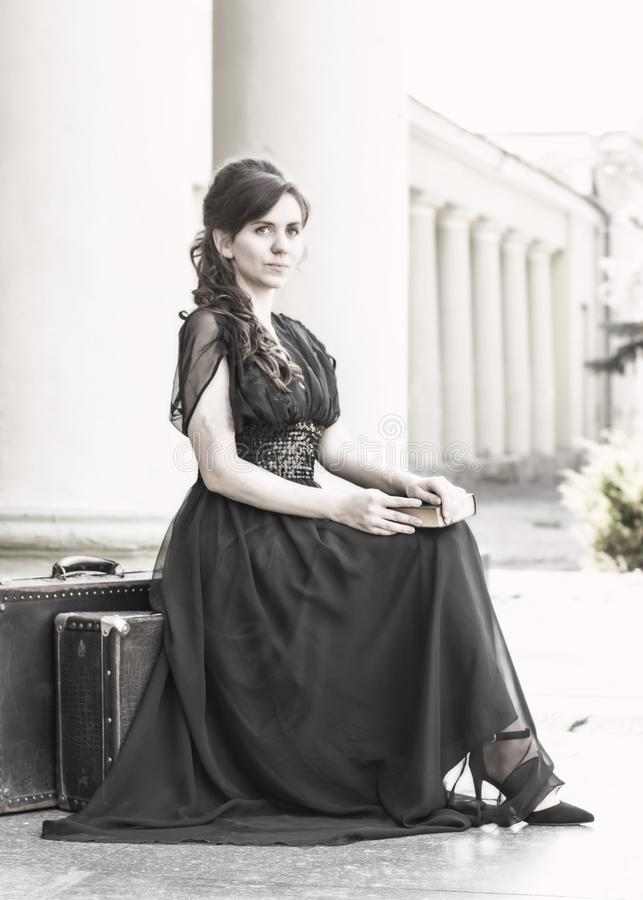 Beautiful girl in a black evening dress sits with a book. A girl sits with suitcases near an old building with columns. Beautiful royalty free stock photo