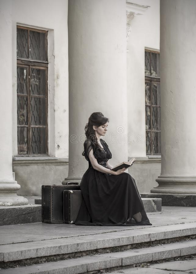 Beautiful girl in black evening dress sitting reading a book. A girl sits with suitcases near an old building with columns. stock images