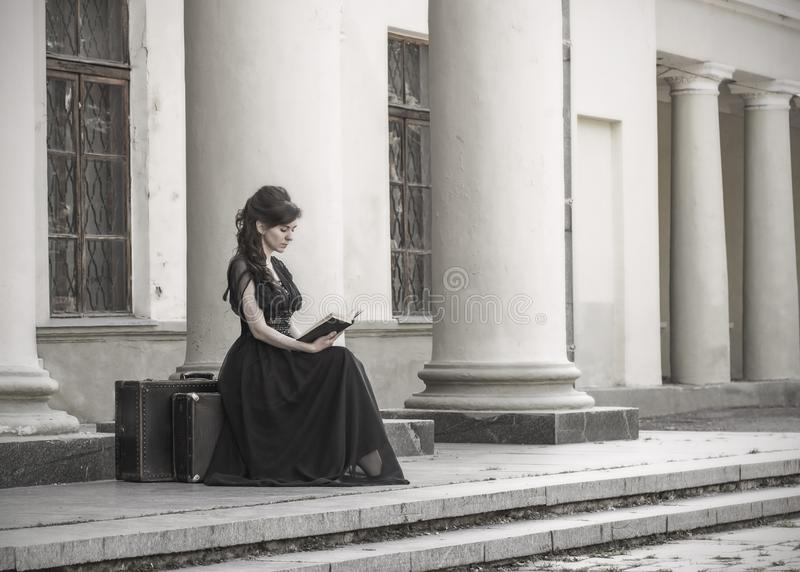 Beautiful girl in black evening dress sitting reading a book. A girl sits with suitcases near an old building with columns. stock image