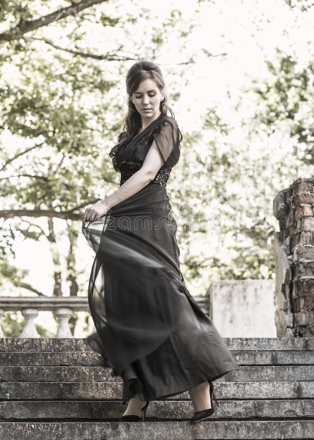 Beautiful girl in a black evening dress on the steps of an abandoned palace. Pretty woman with scars. Young girl in retro style. royalty free stock photos