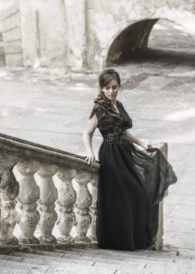 Beautiful girl in a black evening dress on the steps of an abandoned palace. Pretty woman with scars. Young girl in retro style. royalty free stock photography