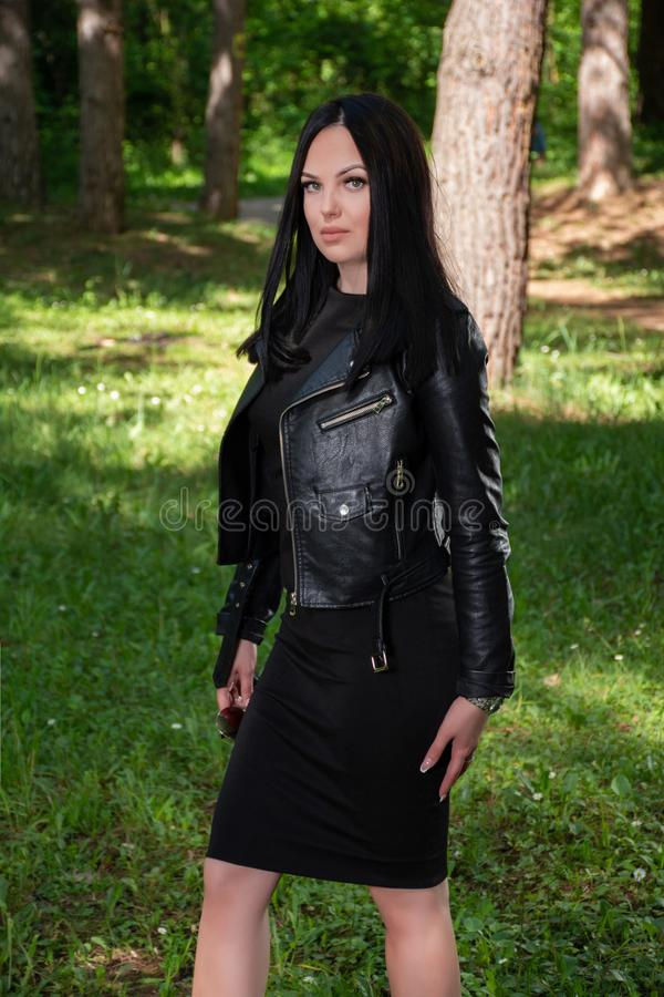 Beautiful girl with black hair, dress and leather jacket in the forest on a sunny spring day stock photography