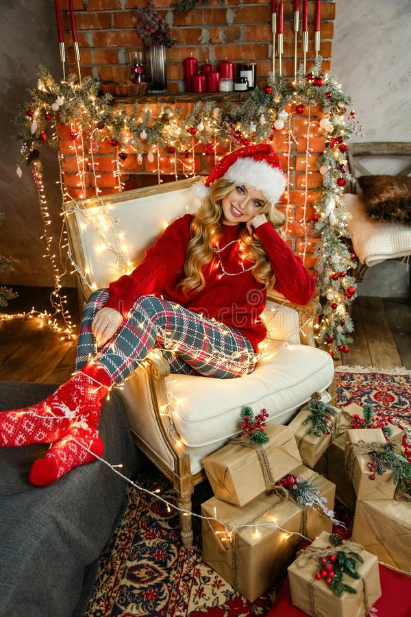 Beautiful girl with blond hair in elegant dress posing in decorated room with Christmas tree and presents stock images
