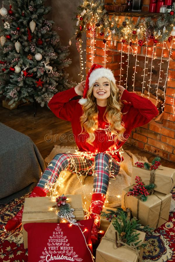 Beautiful girl with blond hair in elegant dress posing in decorated room with Christmas tree and presents stock photography