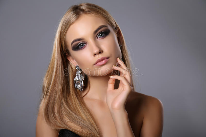Beautiful girl with blond hair and evening makeup with bijou. Fashion studio portrait of beautiful girl with blond hair and evening makeup with bijou stock images