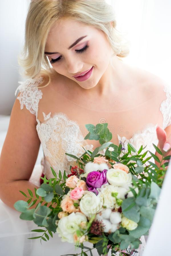Beautiful girl with blond hair in a peignoir elegantly sits on the couch surrounded by flowers royalty free stock photography