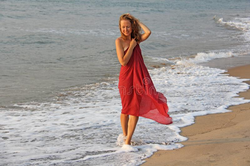 A beautiful girl with blond hair, in a red dress, walks along the seashore and smiles. Summer girl on the sea. Tenderness, alone royalty free stock images