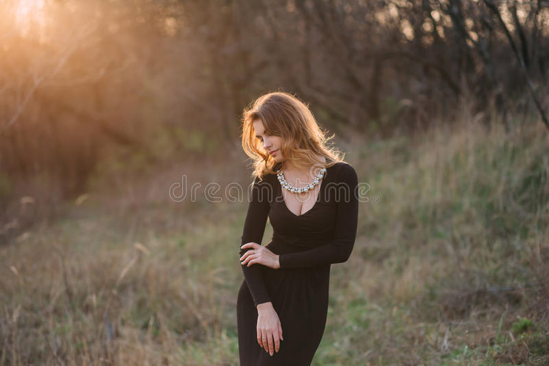 Beautiful girl with blond hair. Standing in a black dress standing on the gothic background blowers forests, forest princess, halloween , dark boho royalty free stock photography