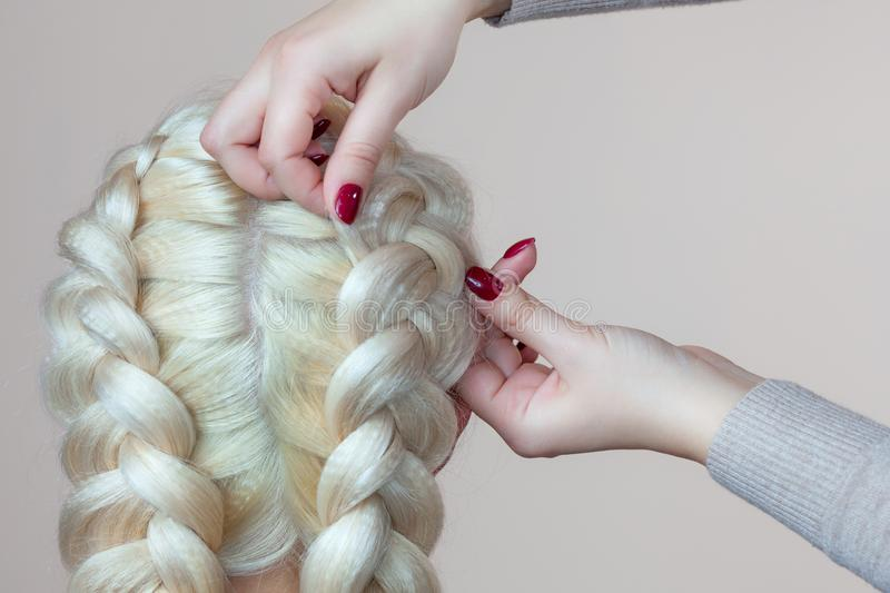 Beautiful girl with blonde hair, hairdresser weaves a braid close-up, in a beauty salon. royalty free stock photos