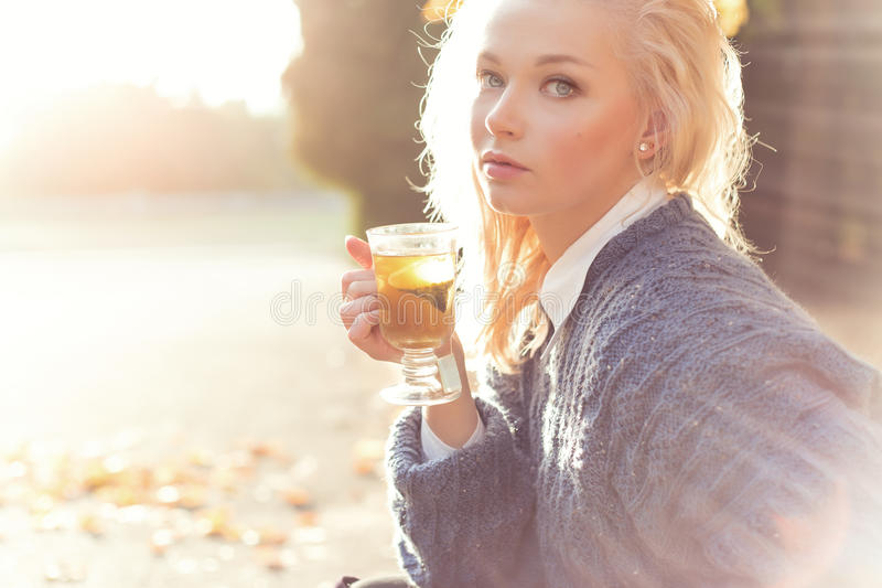 Beautiful girl blonde in warm sweater drinking tea in the Park on a Sunny autumn day in the bright rays of the sun stock image