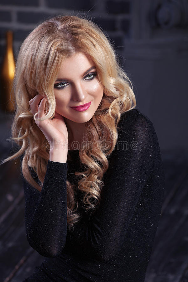 Beautiful girl blonde woman in shikranom black evening dress on a dark background . stock images