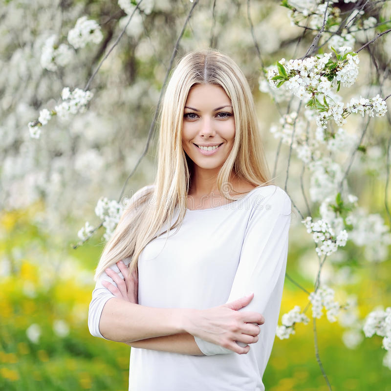 Beautiful girl in blooming tree in spring royalty free stock photo