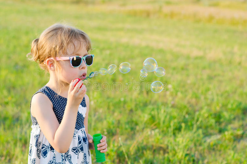 Beautiful girl blowing bubbles in the park, free space. royalty free stock photo