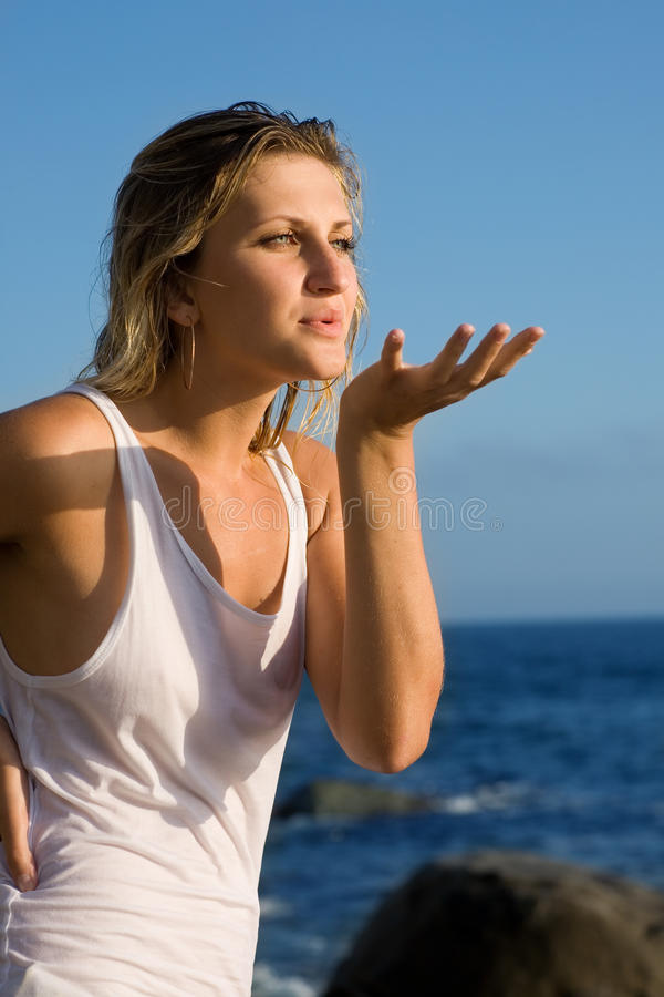 Beautiful girl blowing on the empty hand. royalty free stock photo