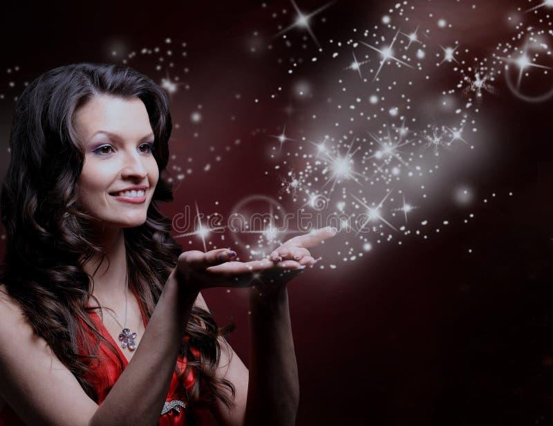 Beautiful girl blowing magic stars. stock photography