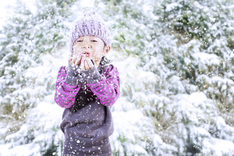 Beautiful girl blowing snow in Christmas. A cute girl with beany is making a wish in Christmas season while snowing outside stock photo