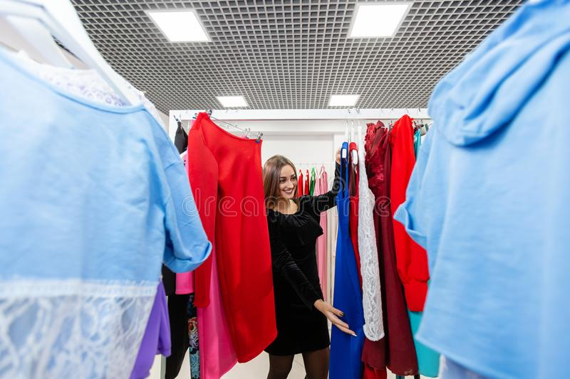 Beautiful girl with blue dress near mirror on room background. Happy young woman choosing clothes in mall or clothing stock images