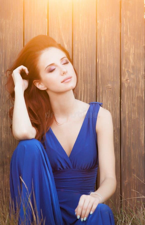 Beautiful girl in blue dress sitting royalty free stock photo