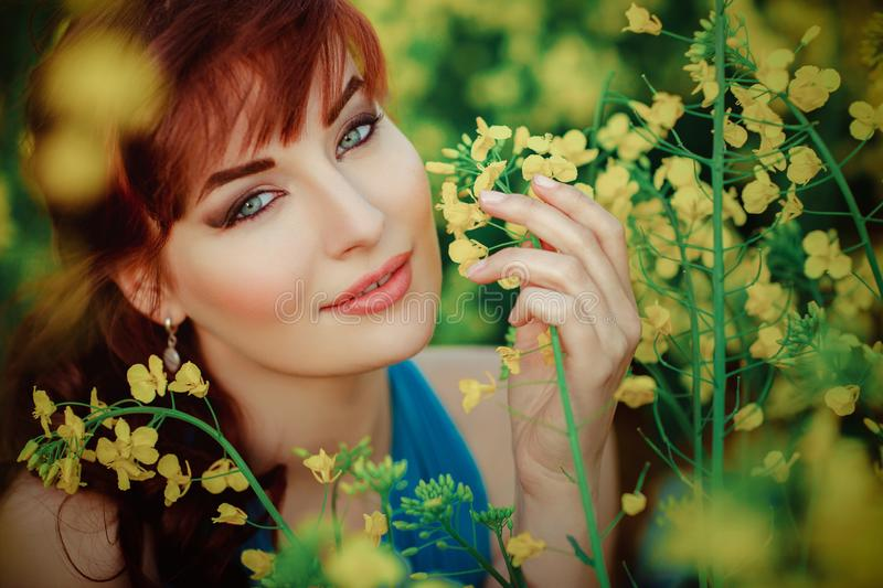 Beautiful girl in blue dress with yellow flowers royalty free stock image