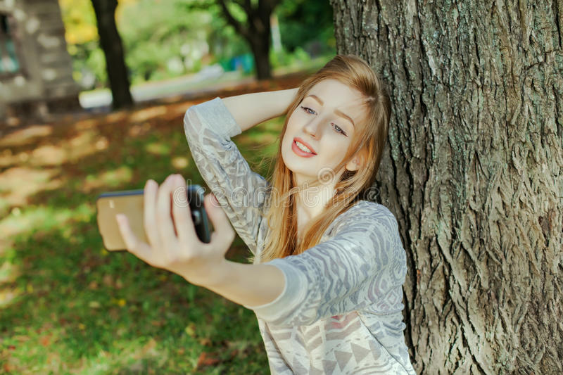 Beautiful girl with blue eyes makes selfie outdoors. Next to the tree and the house royalty free stock photo