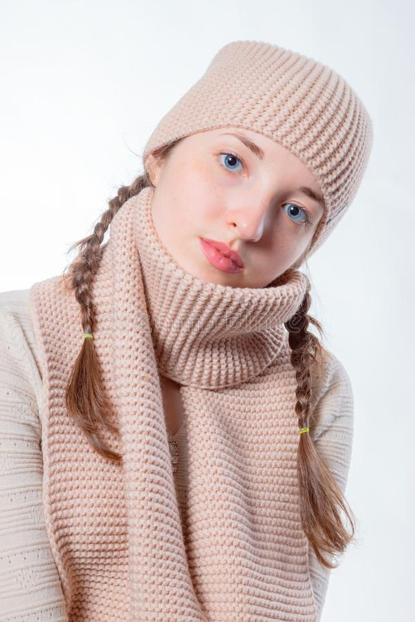 Girl with blue eyes and wicker braids in a knitted hat and scarf. Light background, Cheerful look in the camera royalty free stock images