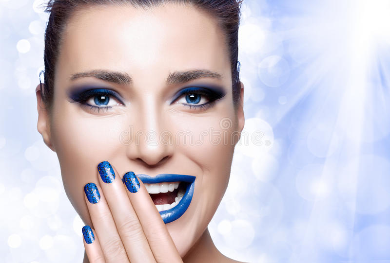 Beautiful Girl in Blue with Hand on Her Face. Nail Art and Makeup concept stock images