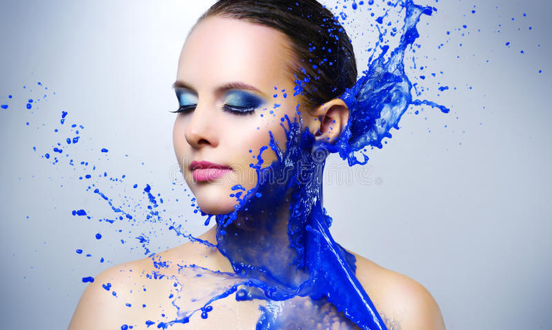 Beautiful girl and blue paint splashes stock photography
