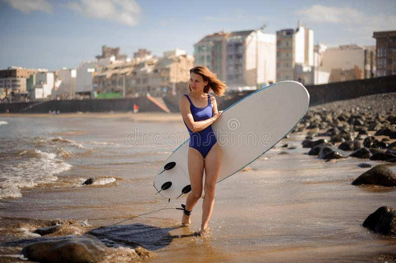Beautiful girl in the blue swimsuit walking with the white surfboard stock photos