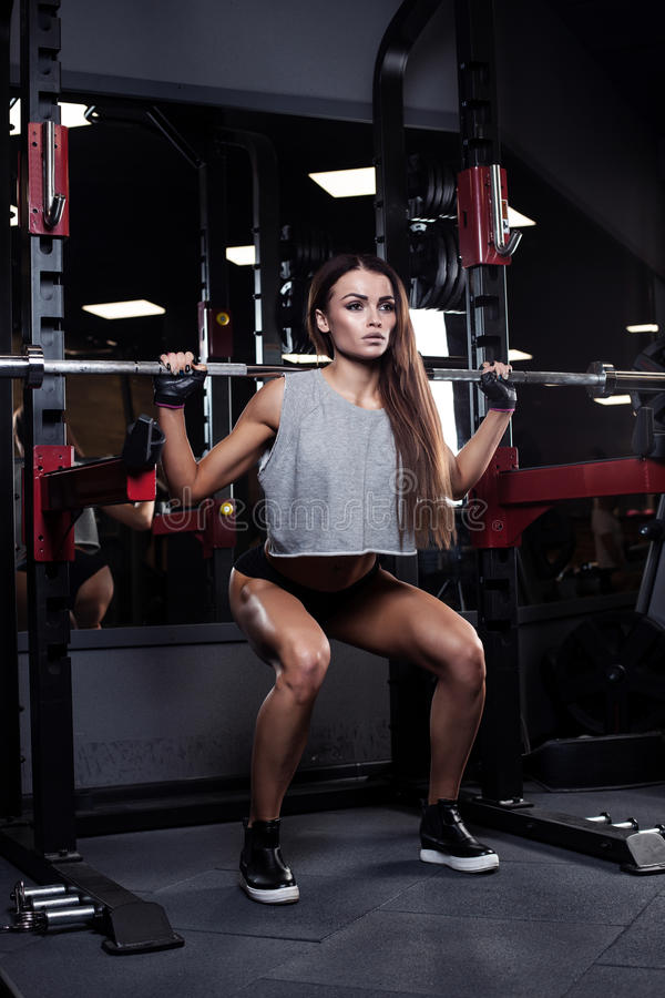 Beautiful girl bodybuilder , execute exercise with dumbbells, in. Beautiful brunette during workout in gym royalty free stock photography