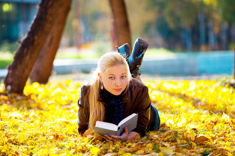 Beautiful girl with book. In the autumn park royalty free stock images