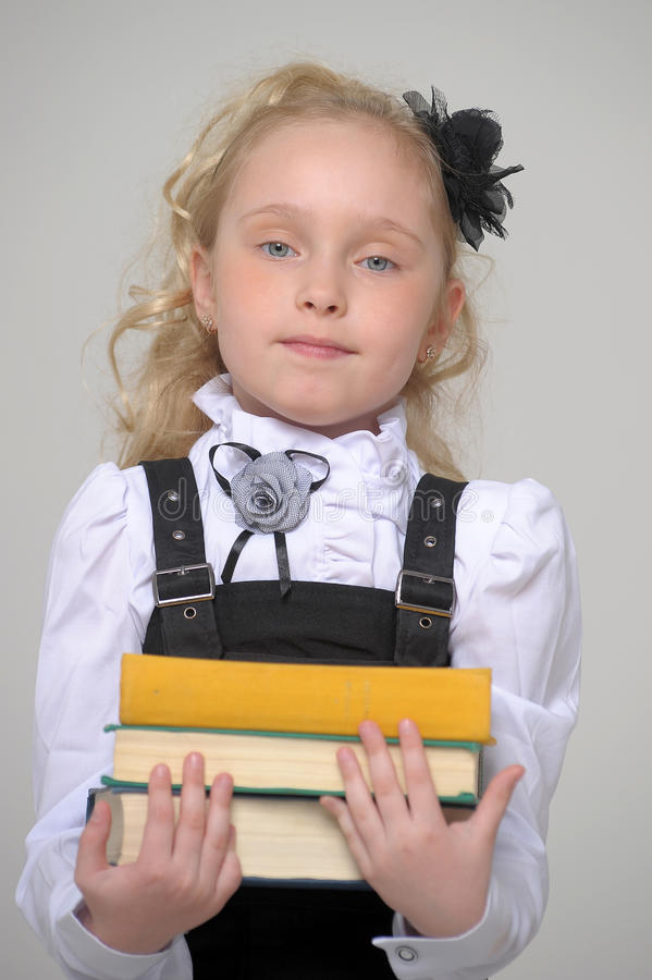 Beautiful girl with book. Schoolgirl girl holding a book in hands stock photography