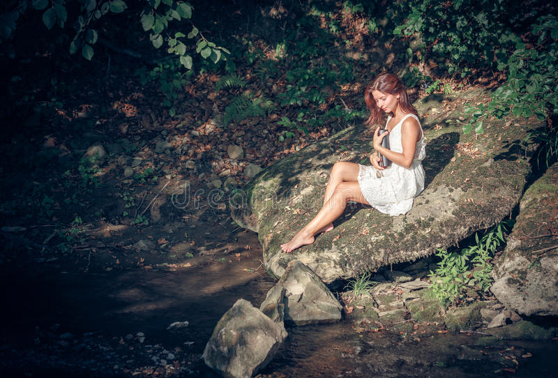Download Girl With Book Onbank Of Small River Stock Photo - Image: 30306936