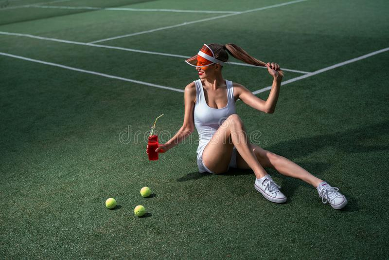 Beautiful girl with a bottle of lemonade on the court stock image