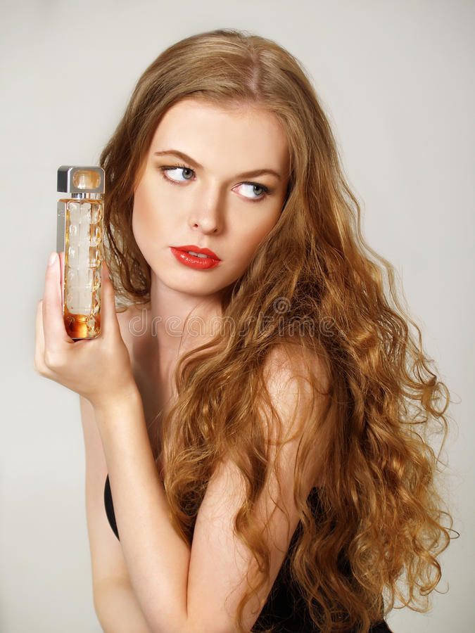 Beautiful girl with bottle of perfume stock photography